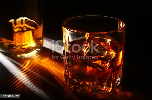 istock Bottle and Glass of whiskey or bourbon with ice on black stone table. 872348972
