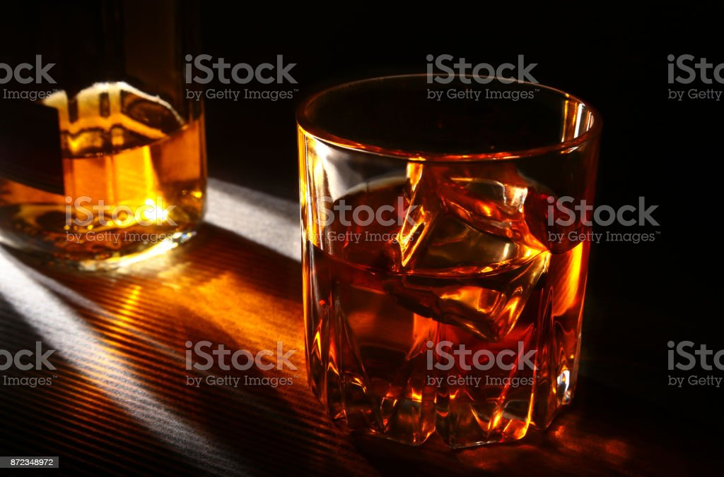 Bottle and Glass of whiskey or bourbon with ice on black stone table. stock photo