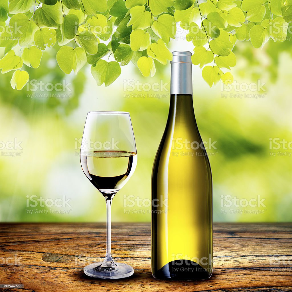 Bottle and glass of white wine on wood table royalty-free stock photo