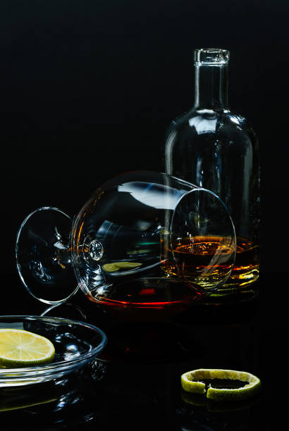 Cтоковое фото Bottle and glass with the remains of alcoholic drink, a saucer with lime pieces