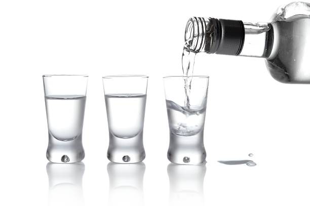 Bottle and glasses vodka poured into glass isolated on white Close-up view of bottle and glasses of vodka poured into a glass isolated on white vodka stock pictures, royalty-free photos & images