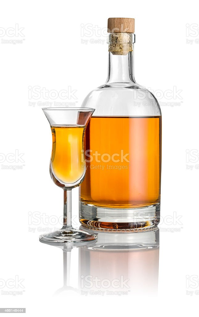 Bottle and high stem glass filled with amber liquid stock photo