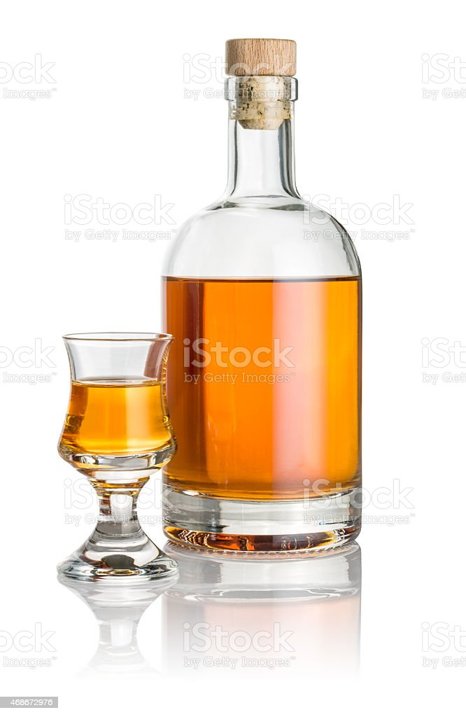 Bottle and schnapps glass filled with amber liquid stock photo