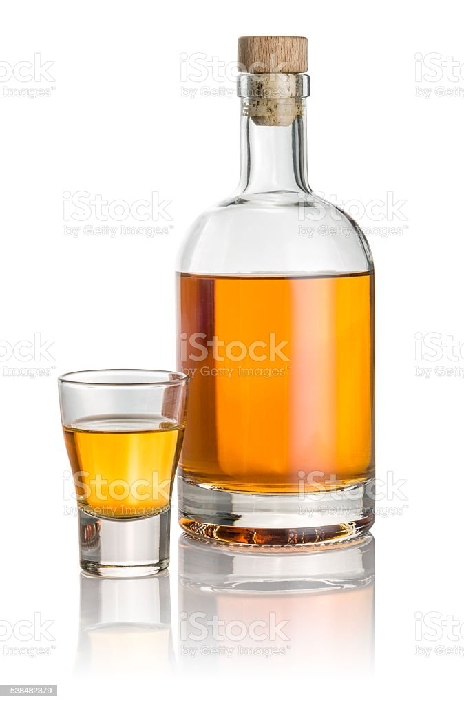 Bottle and shot glass filled with amber liquid stock photo