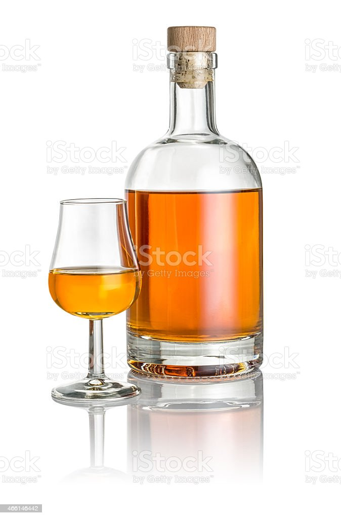 Bottle and snifter filled with amber liquid stock photo