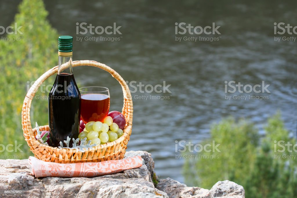 Bottle and the wineglass of wine and the basket with fruits on a rock by the river stock photo