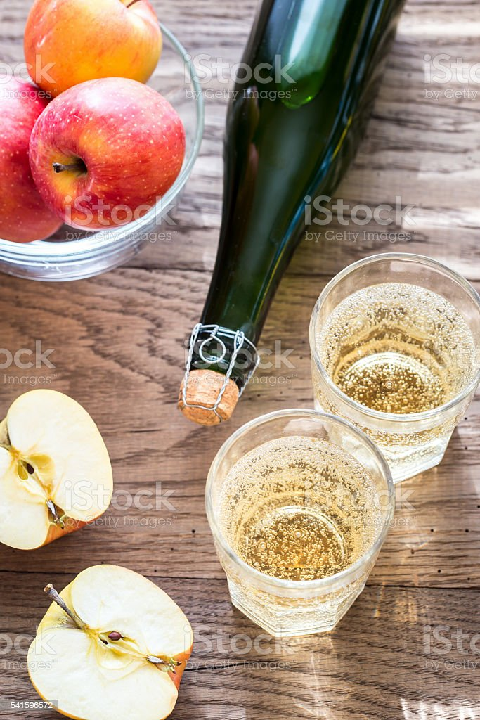Bottle and two glasses of cider on the wooden background – Foto