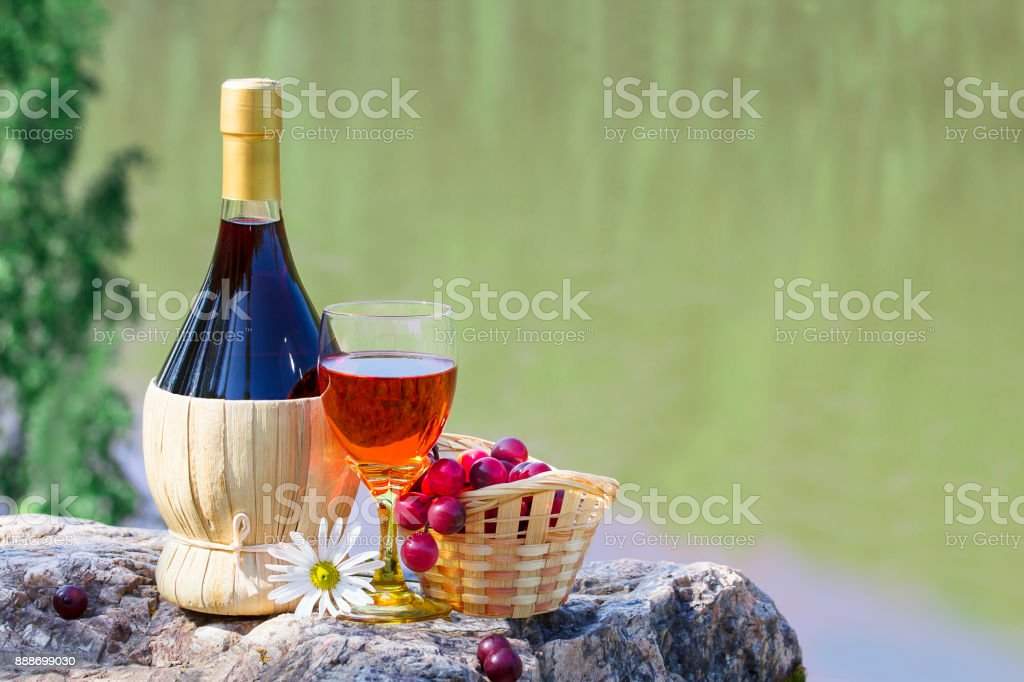 Bottle and wineglass of wine with the basket of grapes on a rock by the river stock photo