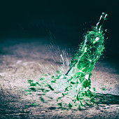 Green wine bottle hitting the floor and breaking.