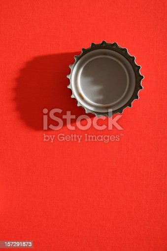 Straight down shot of bottle cap. Hard light and long shadow over red textured paper