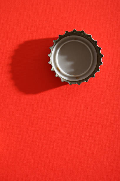 Bottle cap Straight down shot of bottle cap. Hard light and long shadow over red textured paper bottle cap stock pictures, royalty-free photos & images