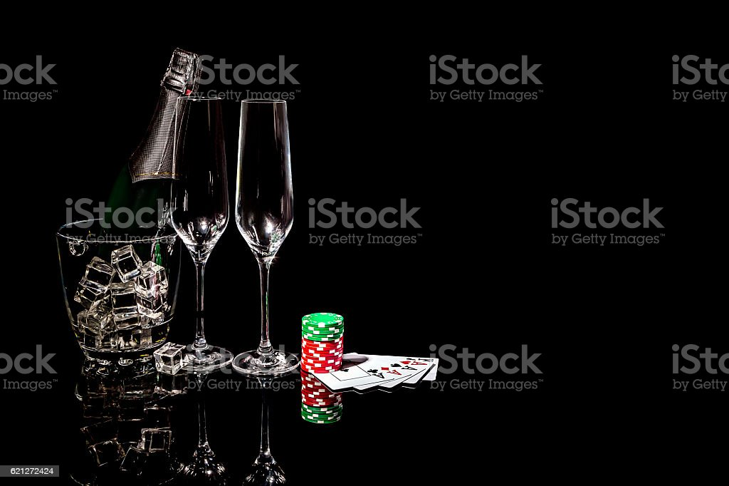 Bottle champagne in ice bucket with wineglasses and cards and chips stock photo
