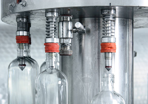 bottle filling. - bottling plant stock photos and pictures