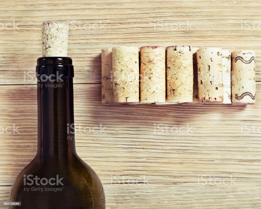 Bottle from dark glass and wine corks on wood royalty-free stock photo