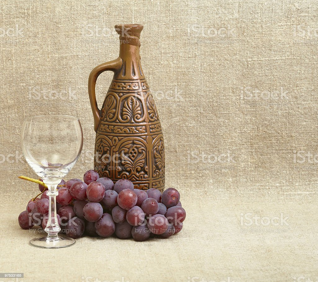 Bottle, grapes and a glass on canvas royalty-free stock photo