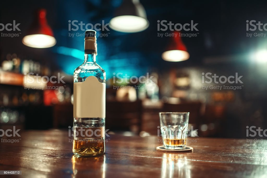 Bottle of alcohol and glass on bar counter closeup stock photo