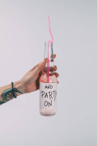 flasche alkohol getränk in der hand - partylabels stock-fotos und bilder