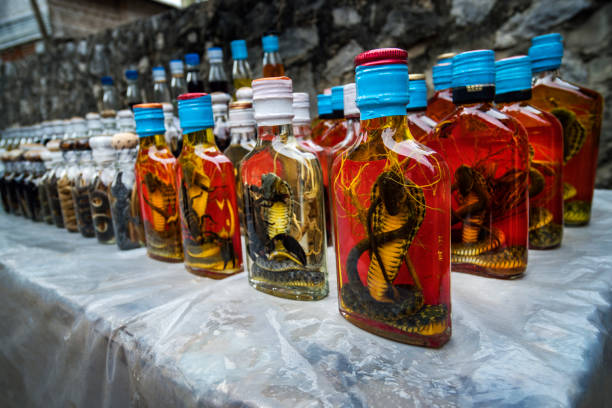 Bottle of Alcohol containing liquor with cobra snake and scorpion inside on a market stock photo