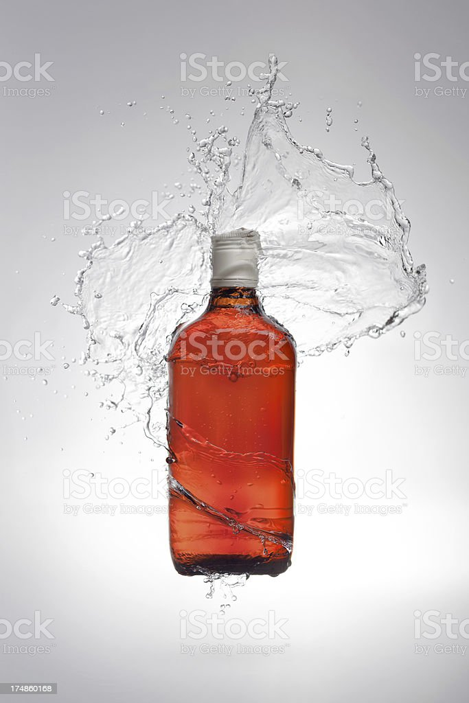 Bottle of alcohol with water splash royalty-free stock photo