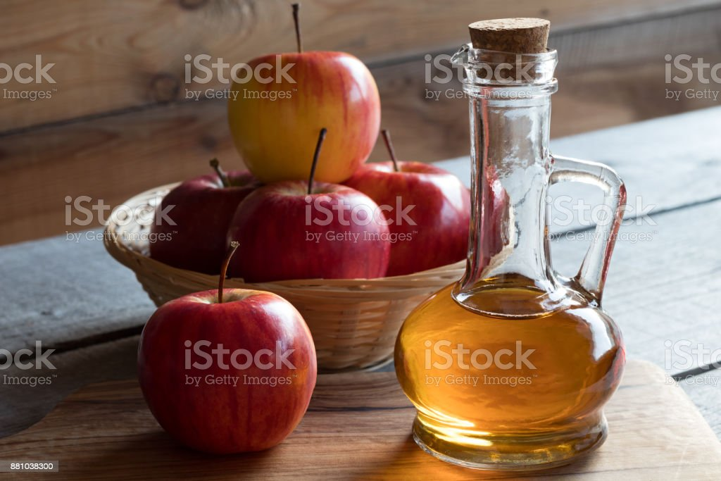 A bottle of apple cider vinegar with apples stock photo
