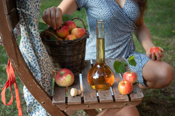 A bottle of apple cider vinegar with fresh apples A bottle of apple cider vinegar in a garden, with a woman in the background apple cider vinegar stock pictures, royalty-free photos & images