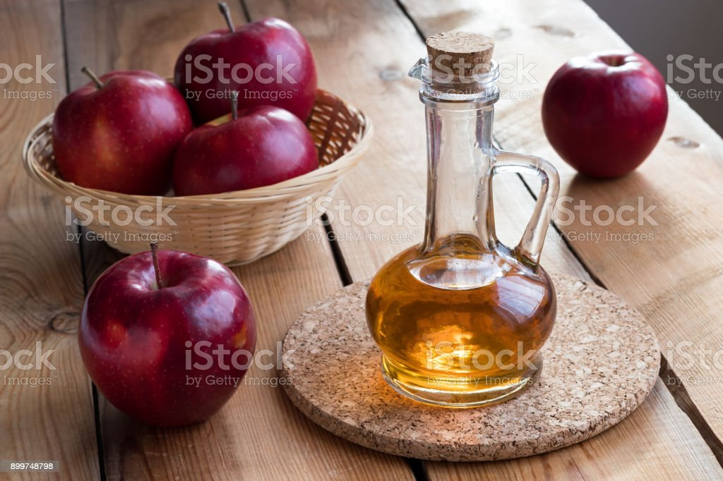 A bottle of apple cider vinegar with red apples stock photo