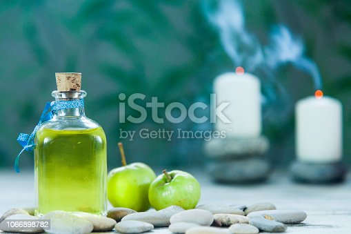 bottle of apple oil massage, river pebbles, two small green apples and two candles with smoke on wooden table and herbal background