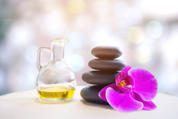 bottle of aroma essential oil with candle and flower on stone table, spa concept. stock photo