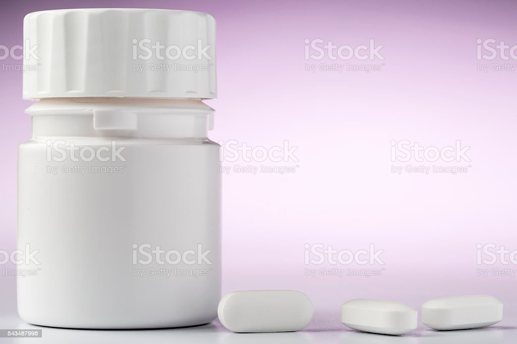 Bottle of aspirin drugs and three pills in the foreground stock photo