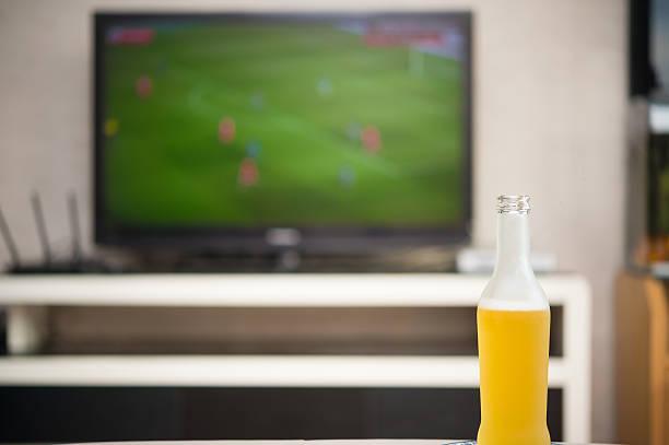 bottle of beer and tv broadcasting a soccer match - fußball themenzimmer stock-fotos und bilder