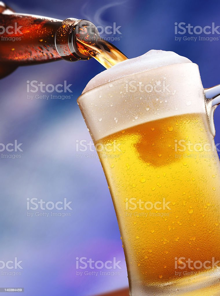 A bottle of beer being poured into a mug royalty-free stock photo