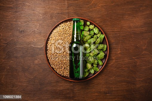 istock A bottle of beer on a green fresh hop and wheat grain in a plate against the wooden brown board 1095021354