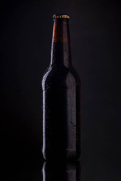 Flasche Bier mit Tropfen auf dunklem Hintergrund. – Foto