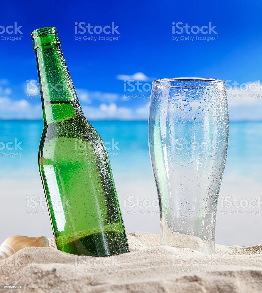 Bottle of beer with empty glass in sand at beach stock photo