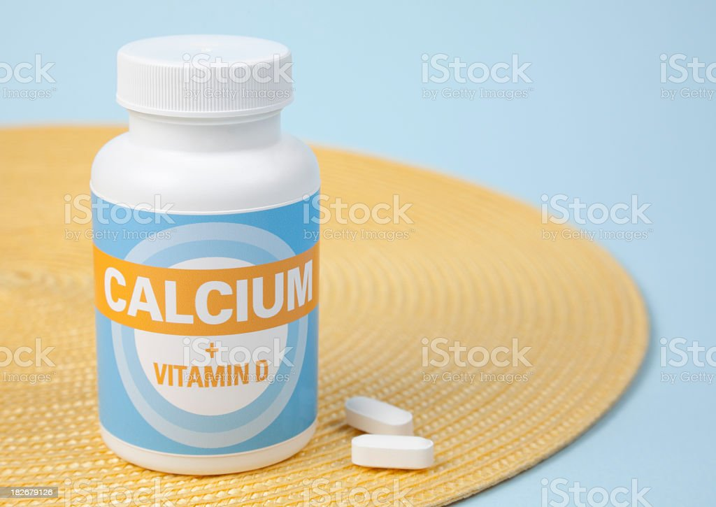 Bottle of calcium tablets on a yellow placemat on table stock photo