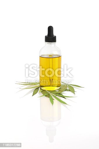 Close-up of Bottle of CBD Oil with hemp leaf on white background