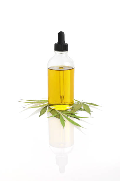 Bottle of CBD Oil with hemp leaf Close-up of Bottle of CBD Oil with hemp leaf on white background tincture stock pictures, royalty-free photos & images