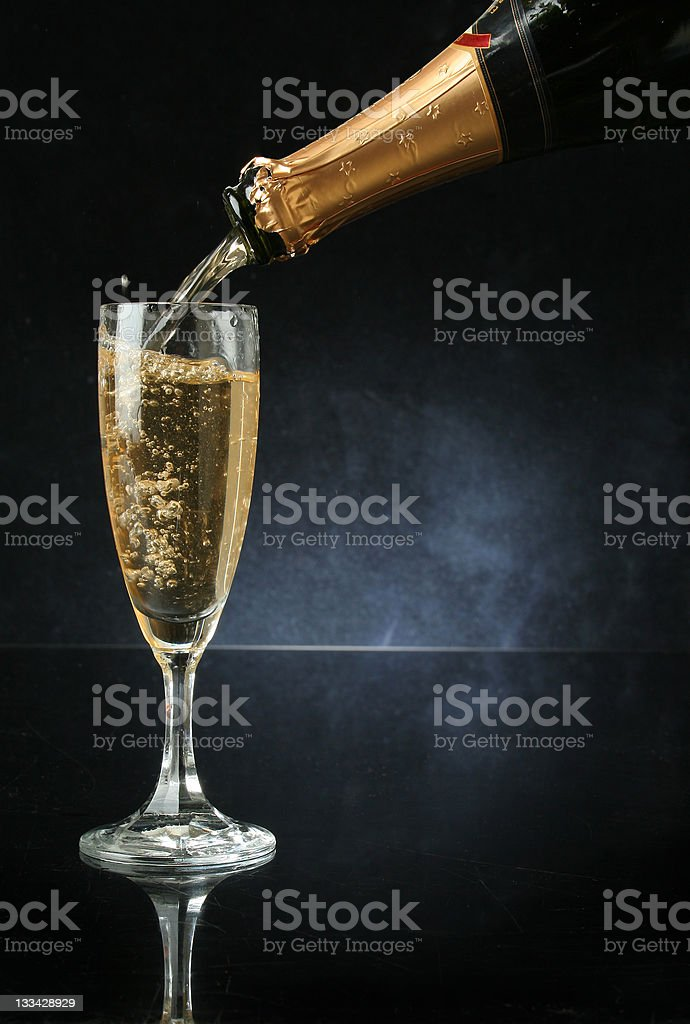 A bottle of champagne being poured into a champagne flute royalty-free stock photo