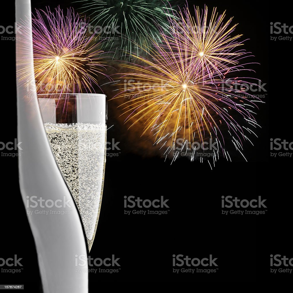 Bottle of Champagne, glass of Champagne on multicoloured fireworks background royalty-free stock photo