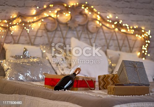 istock Bottle of champagne in bed. Christmas party. gifts and drinks on the bed, Merry Christmas. No people. 1177506460