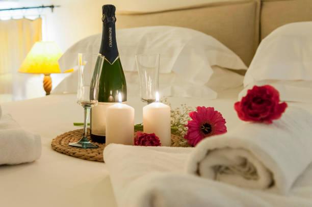 şişe şampanya yatakta - romantiklik stok fotoğraflar ve resimler