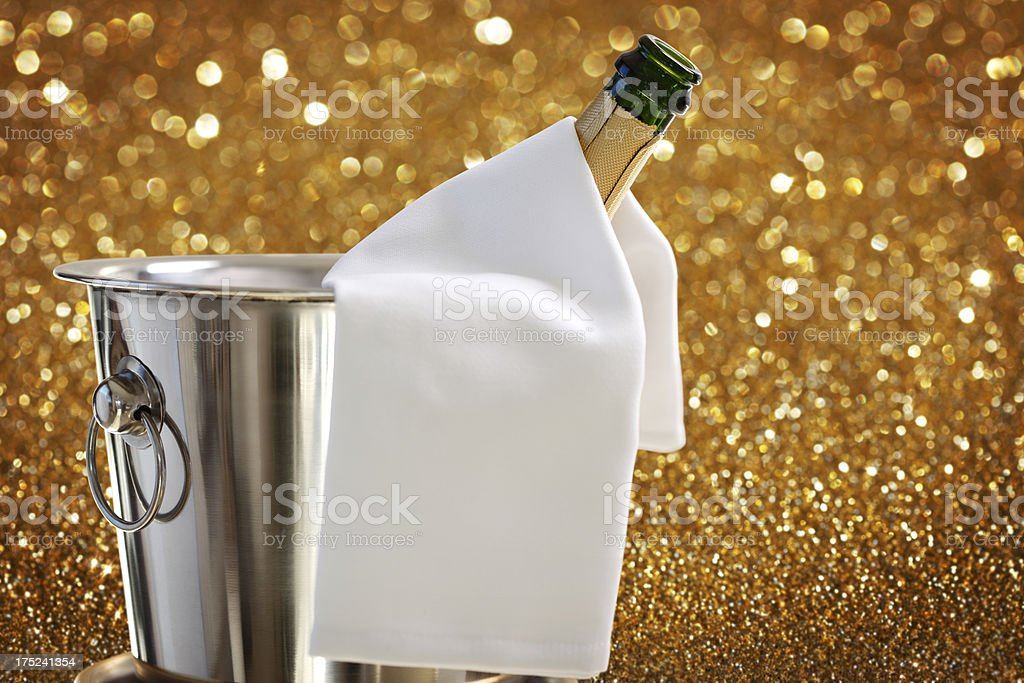 Bottle of Champagne in Ice Bucket against Defocused Background royalty-free stock photo