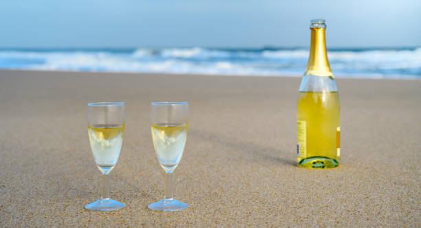 flasche sekt mit zwei gläsern auf sand am strand von sylt, deutschland - urlaub norderney stock-fotos und bilder