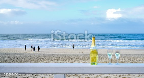 873264516istockphoto Bottle of champagne with two glasses on wooden railing at beach of Sylt, Germany 1083286400