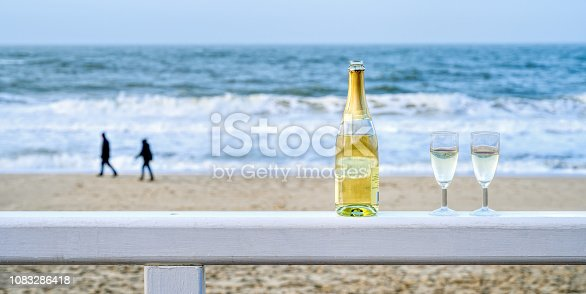 873264516istockphoto Bottle of champagne with two glasses on wooden railing at beach of Sylt, Germany 1083286418