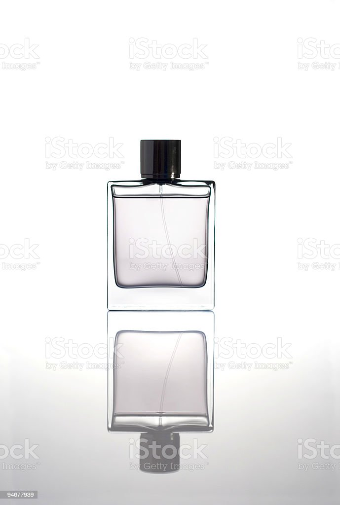 Bottle of clear perfume reflecting off the floor stock photo