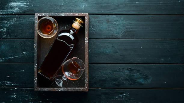 Uma garrafa de conhaque e de vidros em um fundo preto. Brandy. Vista de cima. Espaço livre para o seu texto. - foto de acervo