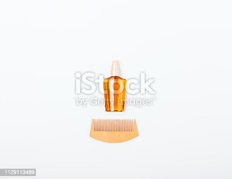 istock Bottle of cosmetic oil next to wooden comb 1129113489