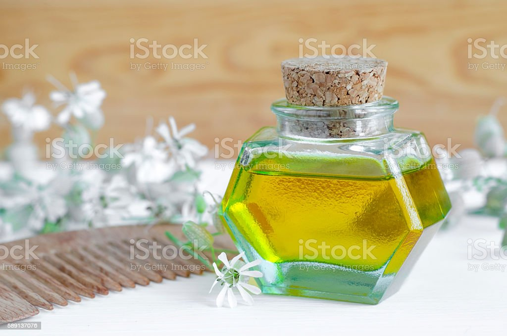 Bottle of cosmetic oil with flowers extract and hair comb stock photo