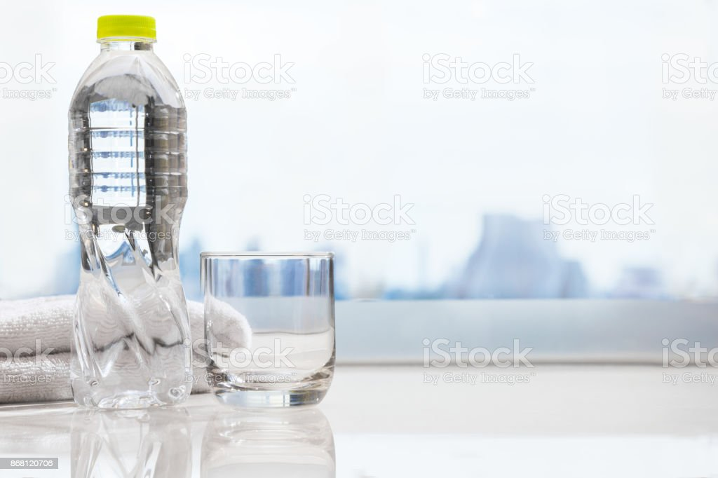 bottle of drinking water and clear drinking glass with white clean...